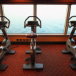 Large gym hall with exercise bicycle near window with view on se — Stock Photo