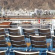 Brown beach chairs on blue ship deck in port near mountains — Stock Photo