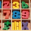 Stock Photo: Math game for junior age with colored wooden signs of numbers ho
