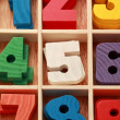Stock Photo: Math game for junior age with colored wooden signs of numbers ve