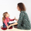 Little girl and her mother sitting on white fell, looking to eac — Stock Photo