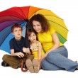 Mother, daughter and son with big multicolored umbrella sitting — Stock Photo