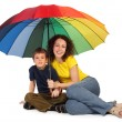 Mother and son with big multicolored umbrella sitting isolated o — Stock Photo #7936829