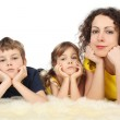 Mother with two serious children lies on white fell studio shoot — Stock Photo #7936833