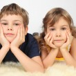 Little boy and girl lying on white fell, chin on hands, looking — Stock Photo #7936835