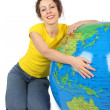 Young beauty woman sitting near big inflatable globe and smiling — Stock Photo #7936839