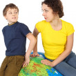 Mother and son sitting on big inflatable globe and looking to ea — Stock Photo