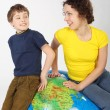 Mother and son sitting on big inflatable globe, smiling and look — Stock Photo #7936859