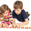 Little boy and girl playing with wooden railway, lying on floor, — Stock Photo