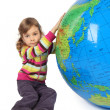 Little girl sitting near big inflatable globe and holding it, lo - Stock Photo