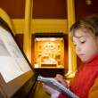 Stock Photo: Little girl standing near monitor writes to writing-books at exc