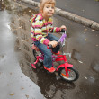 Girl goes on a bicycle on wet asphalt — Stock Photo #7936902