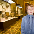 Boy at excursion in historical museum near exhibits of ancient r — Foto Stock