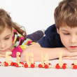 Little boy and girl lying on floor and playing with wooden alpha — Stock Photo