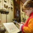 Stock Photo: Little girl writes to writing-books at excursion in historical m