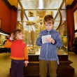 Boy and little girl at excursion in historical museum near exhib - Stock fotografie