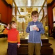Boy and little girl at excursion in historical museum near exhib - Zdjcie stockowe
