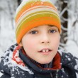 Boy in cap with snow on shoulders in wood in winter — Stock Photo