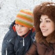 Smiling pretty woman and cheerful boy in winter in wood — Stock Photo #7937038