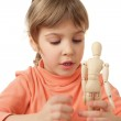Pretty little girl is played by wooden little manikin isolated o — Stock Photo
