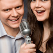 Young beautiful woman and smiling man sing in microphone - Stock Photo