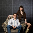Beautiful woman and man sitting in magnificent armchair — Stock Photo