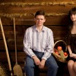 Young man and woman near basket of fruit sitting on bench — Stock Photo