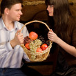Smiling man and woman with basket of fruit sitting on bench — Stock Photo