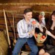 Smiling man and woman with basket of fruit sitting on bench — Stock Photo #7937289
