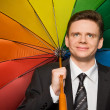 Smiling businessman in suit with multi-coloured umbrella — Stock Photo