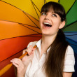 Laughing young brunette woman in white blouse with multi-coloure - Stock Photo