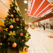 Fur-tree densely covered by Christmas ornaments in shopping cent — Foto Stock