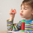 Little caucasian girl in multicolored shirt blowing soap bubbles — Stock Photo