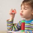 Stock Photo: Little caucasigirl in multicolored shirt blowing soap bubbles
