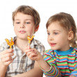Little boy and girl holding lollipops and looking on it, half bo — Stock Photo #7937511
