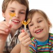 Little boy and girl holding lollipops ,looking on it and laughin - Stock Photo