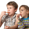 Little boy and girl eating lollipops and looking at left side, h — Stock Photo