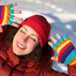 Young beauty girl in multicolored mittens smiling and putting ha — Stock Photo