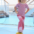 Little girl with yellow ball standing near football goal on crui - Stock Photo