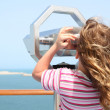 Little girl standing on cruise liner deck and looking in binocul - Stock Photo