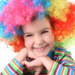 Little girl in clown wig smiling and looking at camera, chin on — Stock Photo #7937803