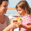 Mother and daughter standing on cruise liner deck, mother holdin - Stockfoto