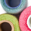 Fragment of three coils with multi-coloured sewing threads isola - Stock Photo