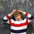 Pupil standing near school board and hold on his head half body — Stock Photo #7938092