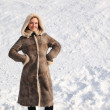 Young beauty woman in long coat standing on snowy area and smili — Stock Photo