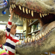 Little boy and girl looking in tyrannosaurus opened mouth focus — Stock Photo