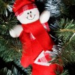Smiling toy snowman in red clothes hanging on Christmas fur-tree - Stock Photo