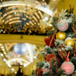 Fur-tree densely covered by Christmas ornaments in shopping cent - Stock Photo