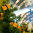 Three celebratory gifts in yellow boxes hanging on Christmas fur - Stock Photo