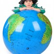 Boy in historical dress leans on inflatable globe chin on hands - Стоковая фотография